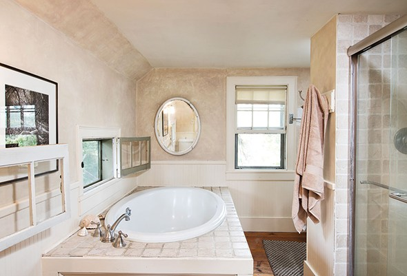 Upstairs, Shaff captured space from a front bedroom to build her dream bathroom. This includes a soaking tub with bird's eye view out the casement windows. - DEBORAH DEGRAFFENREID