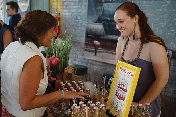 Maya MacLaughlin of Maya's Jams speaks with a guest about her syrups. - JOHN GARAY