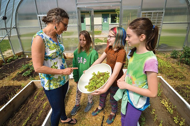 Students in the Oakwood school greenhouse work with a Poughkeepsie Farm Project educator.