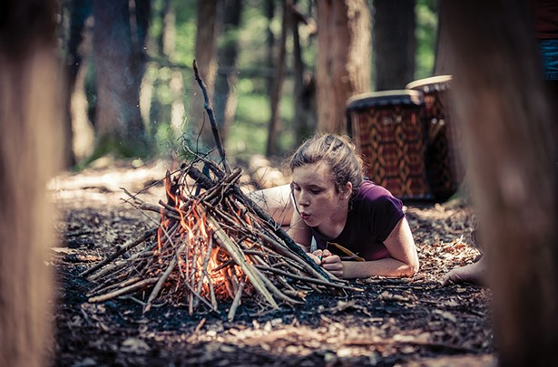 Student tending a fire at a Wild Earth program.