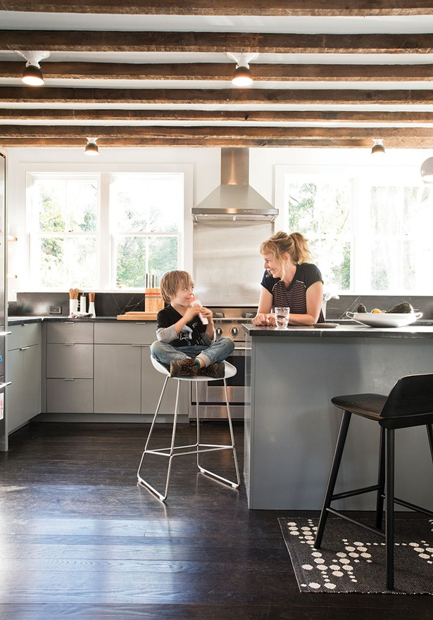 """Dunja Von Stoddard and her son Lars in the kitchen. The space was rebuilt from the ground up (including the south facing back wall, which had sustained fire damage and needed to be completely replaced), but the wooden ceiling beams are original.""""I wanted to bring it back in a modern way that was still appreciative of an old farmhouse,"""" says Von Stoddard. - DEBORAH DEGRAFFENREID"""
