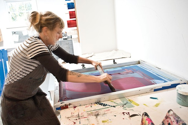 "Von Stoddard in the studio at her screen printing press. Between caring for her young son and the tasks of daily life, she has little time to waste. She sketches and draws designs at night and then ""cranks out"" the designs during the day. ""Someone asked me 'When are you most creative?' I'm like, 'Whenever I have time.' - DEBORAH DEGRAFFENREID"
