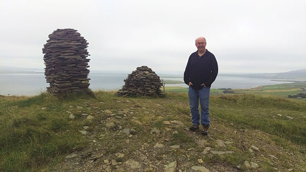 Laird Scranton with cairns atop Cuween Hill in the Orkney Islands off Scotland.