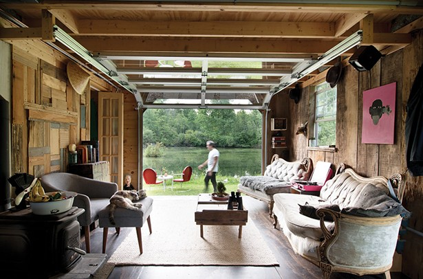 The interior of the couple's studio looks out over the pond. Covelli built the island at the center out of construction netting, leftover wood, and 107 one-gallon containers left behind by the property's previous owners. - DEBORAH DEGRAFFENREID