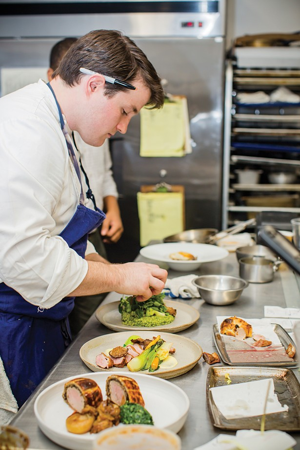 Michael Kelly in the kitchen at Liberty Street Bistro preparing plates of (front to back) pork wellington, roasted duck breast, and barley risotto - PHOTOS BY MARY KELLY