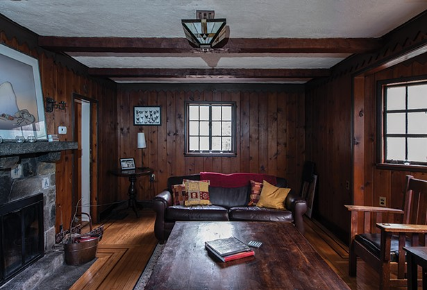 """Stewart has filled the wood paneled den - with art and mementos from her parents and - grandparents. The paned leaded glass window - and Art Deco chandelier are original to the home. """"This really does remind you of an old library,"""" she says. """"It's been nice to introduce things from my family. It gives the space a very warm feeling."""" - PHOTO: DEBORAH DEGRAFFENREID"""