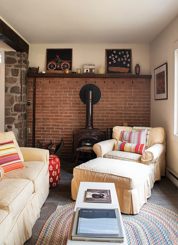 """Former owners added a wood stove to the - downstairs """"great room."""" Stewart has surrounded the space with cozy chairs to create a nook for reading or guests. Since buying the house, she's had many friends - move to the area, and befriended many locals. - PHOTO: DEBORAH DEGRAFFENREID"""