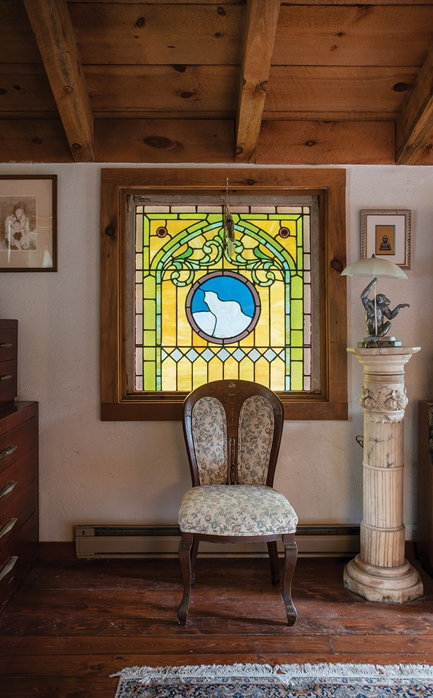 "Blue salvaged two antique windows from a church in Vermont and put them in one of the home's bedrooms. ""I used to go antique hunting and buy stuff at auction,"" he explains. ""The whole house is filled with art I found over - the years."" However, he is ready to let the stuff go and now focus on living things—most especially rescuing animals worldwide. ""I'm selling the art. When you collect things, you don't own them anymore, they own you."" - PHOTO: DEBORAH DEGRAFFENREID"