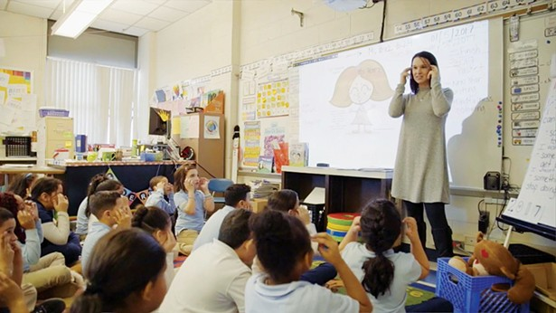 Samantha Alzate, a clinical social worker in New Britain, Connecticut, leads students at Smalley Academy in tapping techniques. - The still is from a documentary of Alex Ortner's visit to the school to read from his book Gorilla Thumps & Bear Hugs.