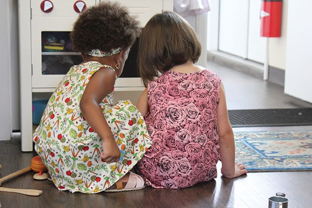 Garyanna and Alessia at play in their comfortable Lucky Bug dresses. Garyanna wears the Veggie Garden print and Alessia wears the Fairy Rose print.