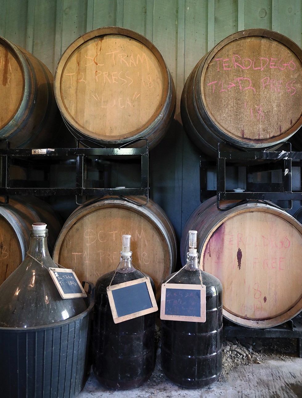 The glass demijohns on the floor hold wine used for topping up the barrels during fermentation and aging. - PHOTO: PETER BARRETT