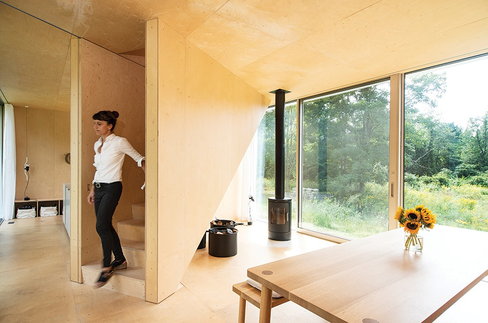 """Betts descending the staircase from the second floor master suite into the home's formal dining area. The couple finished all the home's interior surfaces, including the built-in dining table, benches and kitchen island, with simple plywood. """"We didn't want anything to distract from the geometry of the space or the view of the landscape,"""" she explains. """"But the plywood is beautiful in its own right—it has - its own configuration and pattern to the screws and the paneling."""" - PHOTO: DEBORAH DEGRAFFENREID"""
