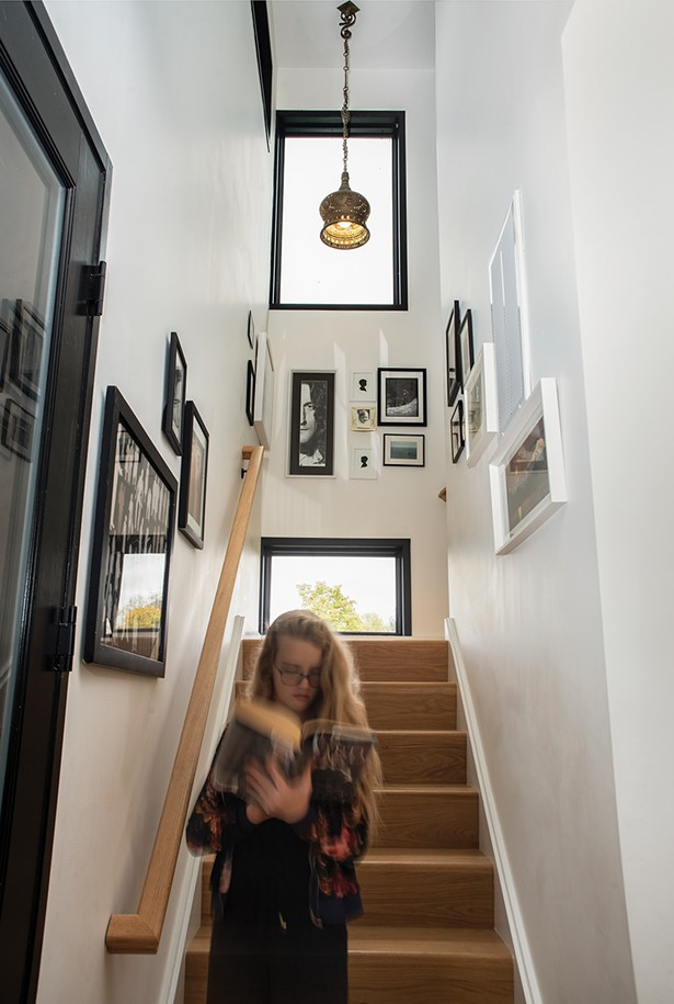 Schmidt's daughter descending the stairs. Her 12'-by-12' foot room upstairs has a distinctive feature: She can climb out the window under the home's overhang to enjoy her own private outdoor reading nook. The stairs are decorated with local artwork, including paper-cut silhouettes by Jenny Lee Fowler of Port Ewen and a pencil drawn portrait of Robert Plant by Raphiel O'Connor of Rhinebeck. - PHOTO: DEBORAH DEGRAFFENREID