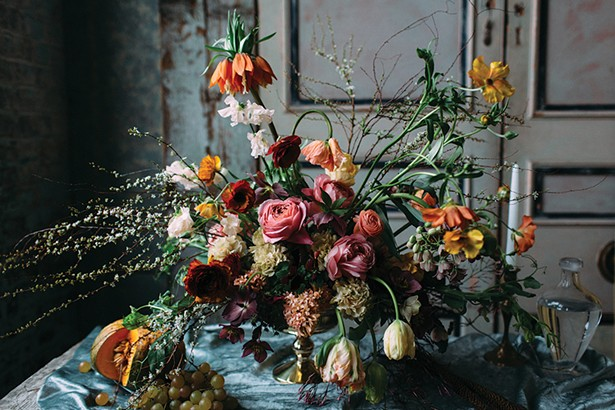 Moody spring floral design by Dark + Diamond, inspired by the Dutch masters. Including blooming spirea branches, fritillaria, parrot tulips, butterfly ranunculus, hyacinth, hellebore and jasmine vines. - COURTESY OF DARK + DIAMOND