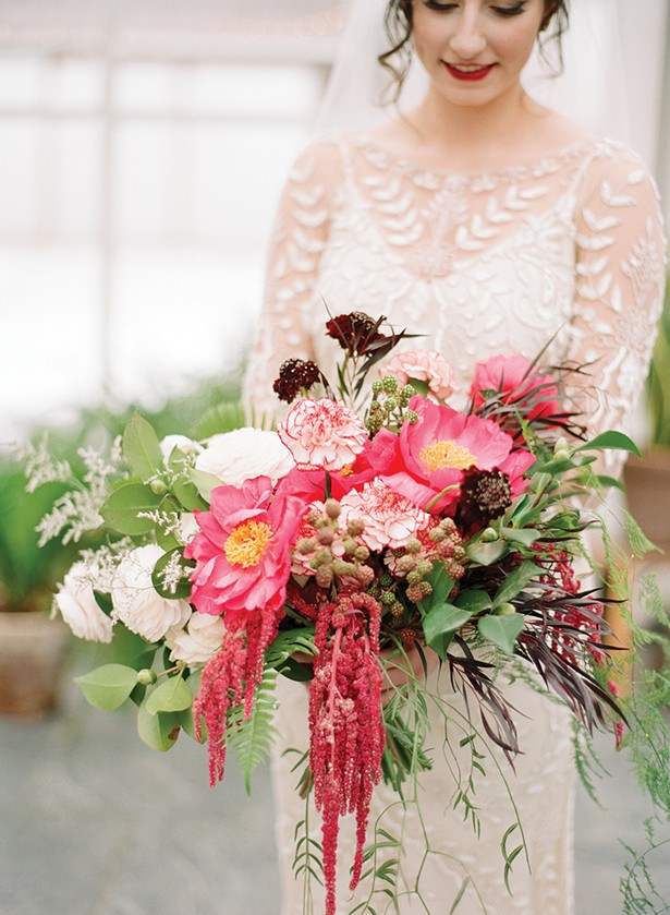 A wild, winter bridal bouquet with peonies, unripe raspberries, ranunculus, scabiosa, hanging amaranthus, camellia, limonium, antique carnations, ferns and cascading pepper berry foliage. - COURTESY OF DARK + DIAMOND