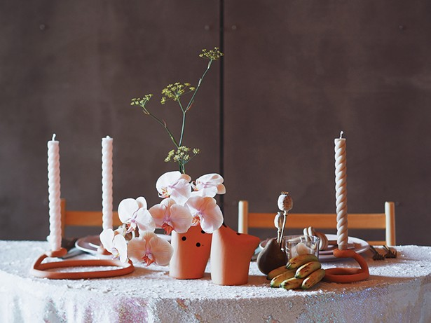 A centerpiece of fennel, orchids, and poppy pods by Heart & Soil.
