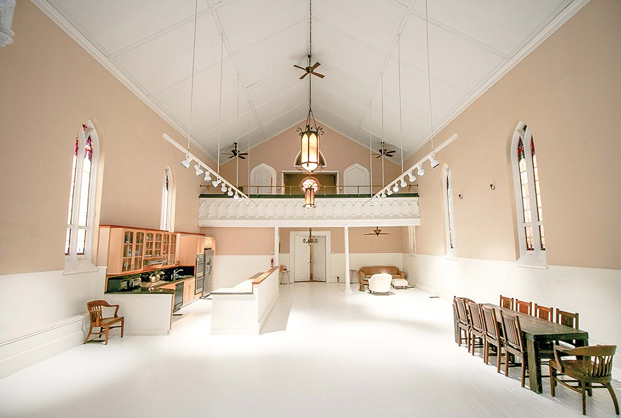 """Bokaer purchased the church in 2016 and has spent the last four years """"listening to the space,"""" he says. He has piloted a few projects—including a small dance performance—and made multiple structural upgrades to the building. Bokaer commissioned the 10-seat wooden parson's table especially for the space and added a - chandelier at the entrance. - PHOTO BY SETH DAVIS"""