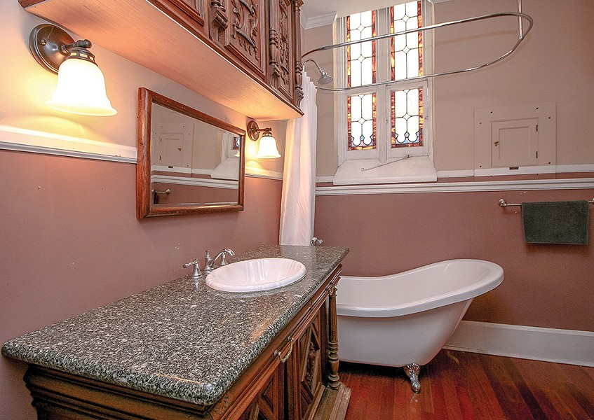 """A freestanding slipper tub sits in a corner of the bathroom under a stained glass window. """"I just loved the slipper tub,"""" says Bokaer. """"As a choreographer, I know how important it is - to take care of the body."""" - PHOTO BY SETH DAVIS"""