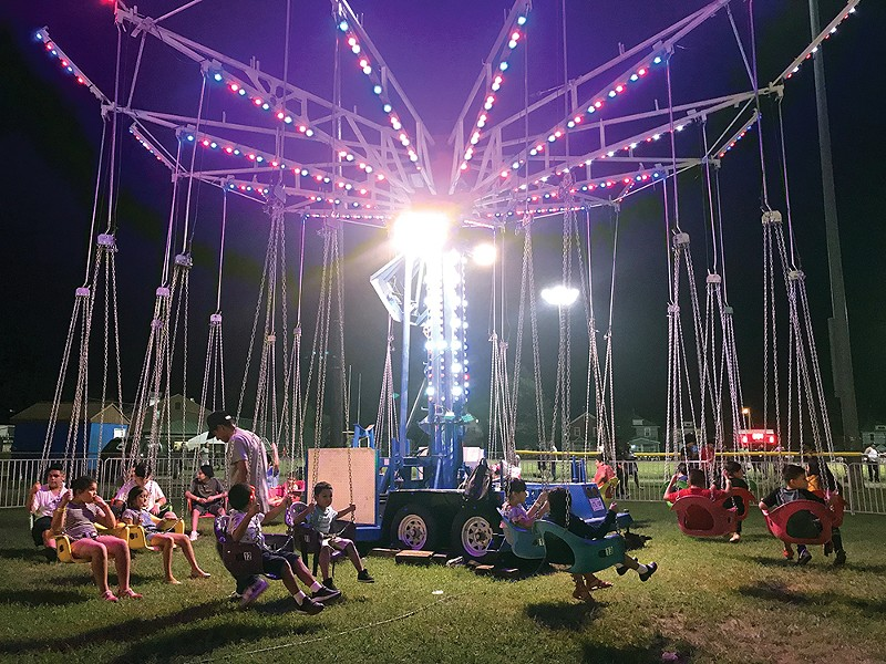 Children enjoying the swing carrousel at Delano Hitch Park. - PHOTO BY STEPHANIE QUISPE