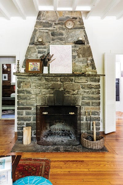 The massive stone fireplace features art by Josef Presser and Tanya Minhas, along with a bouquet of feathers gathered walking the property. - PHOTO: WINONA BARTON-BALLENTINE
