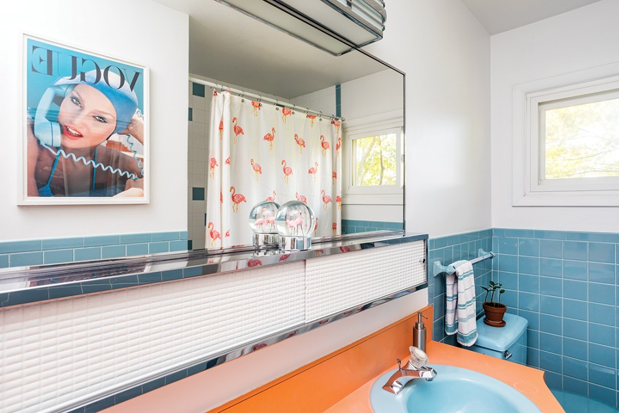 The couple elected to keep one bathroom true to the home's original design, just updating the mirror and some tiles. They framed a vintage Vogue print to complement the bathroom's retro style. - PHOTO BY WINONA BARTON-BALLENTINE