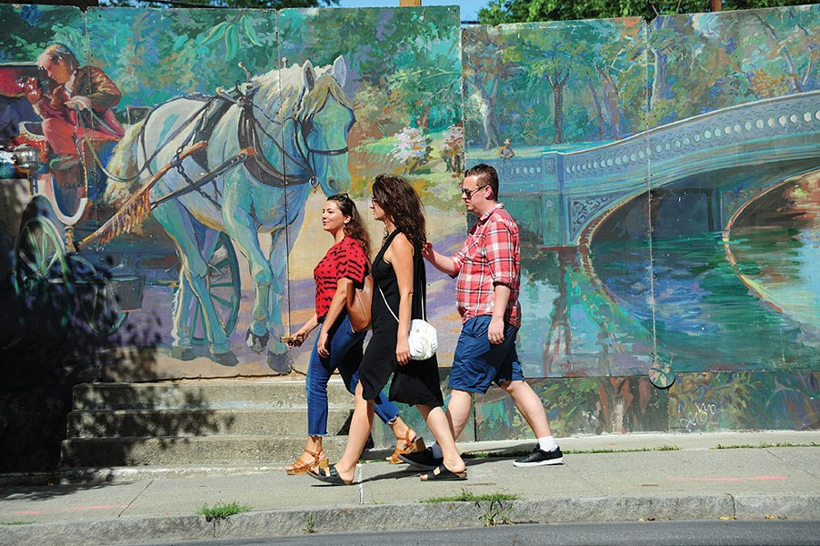 Walking past murals on Warren Street in Hudson. - ROY GUMPEL