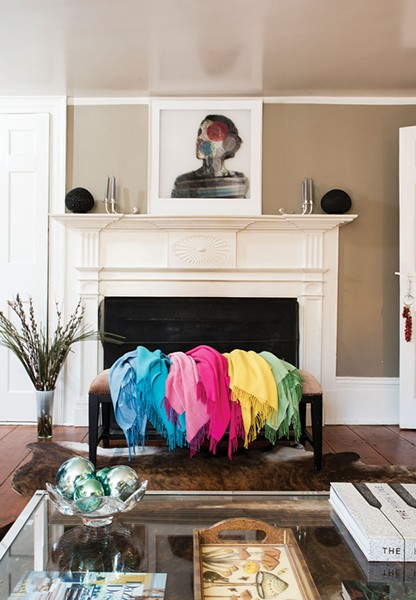 The living room fireplace with a rainbow of shawls. Alpaca fur naturally ranges in 22 different shades. After separating out the guard hair and spinning the fur into yarn, Adams dyes it then weaves it into her signature warm, ultra-soft knit. - DEBORAH DEGRAFFENREID