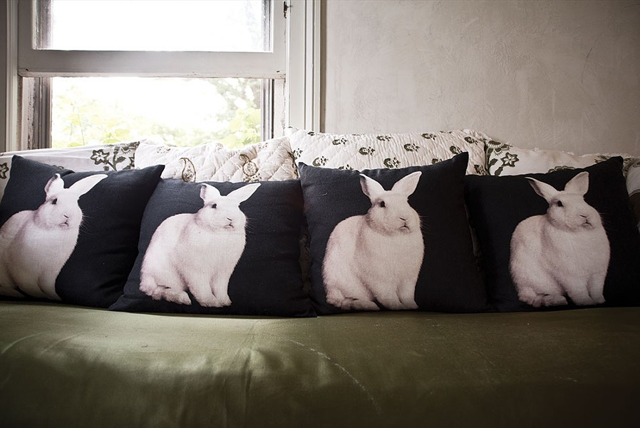 A row of pillows printed with Shaff's bunny portraits. Designed to be affordable and lived with, her compositions are simple yet singular expressions of each animal subject, and by extension, the humans that identify with them.