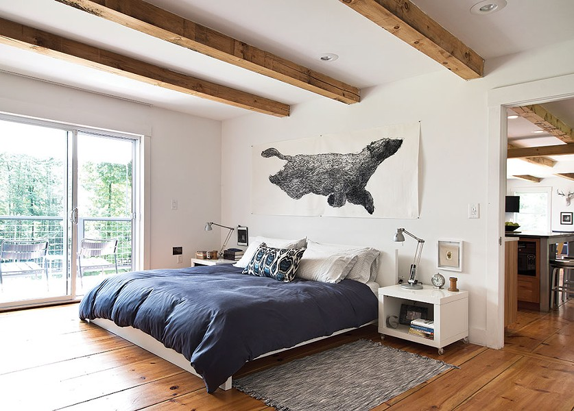 The couple's bedroom overlooks the back deck and is decorated with pieces inspired by their wooded surroundings.The artwork above the bed, Ursa Major Lost At Sea by Aliene De Souza Howell, was purchased from One Mile Gallery in Kingston. - DEBORAH DEGRAFFENREID