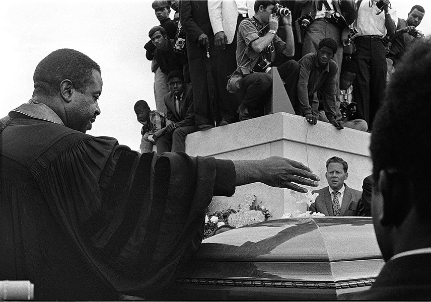 Rev. Ralph Abernathy scatters flowers over the casket of Martin Luther King Jr during burial rites in Atlanta, Georgia, on April 9, 1968. - JIM PEPPLER