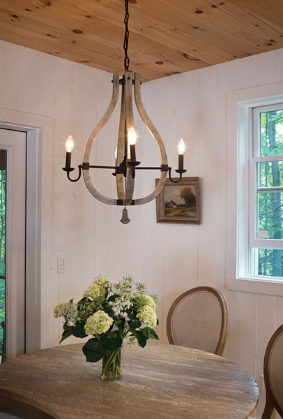 The downstairs dining area looks out over old-growth forest. Nicholas chose the whimsical chandelier from the House of Antique Hardware. Bollman hired local contractors to build the screened in porch. The floors are made from Douglas fir floorboards salvaged from the original cottage. - DEBORAH DEGRAFFENREID