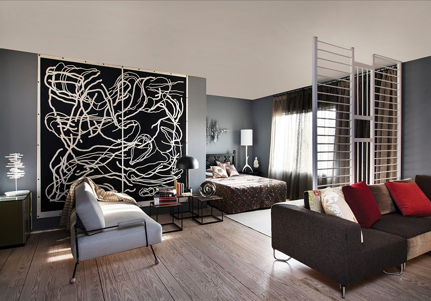 Gillette's living and sleeping area is dominated by a two-panel print by Karl Klingbiel. The headboard is a 1960's lacquered ebony bedroom set. - DEBORAH DEGRAFFENREID