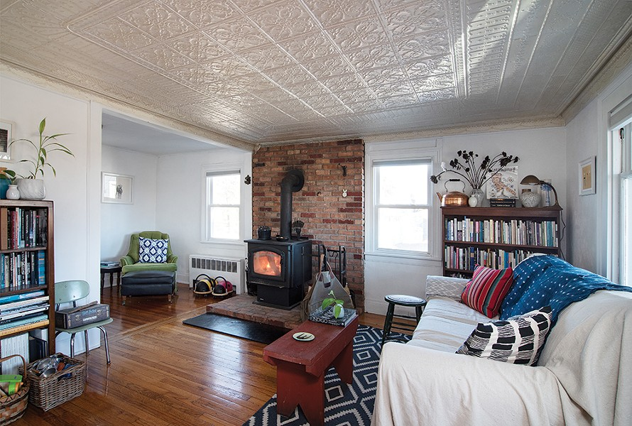 The couple added a wood stove to the front sitting room. The space is decorated with furniture pieces they've collected over the years, as well as pillows and throws handcrafted from natural fibers and hand dyed.