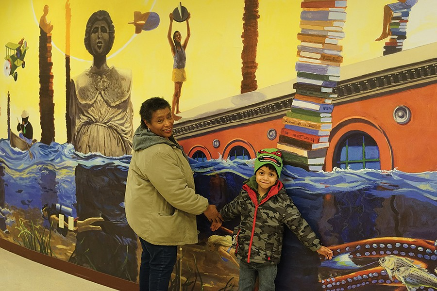 April Coal Blocker and Banicio Sanchez, in front of a mural by James Ransome at the Adriance Memorial Library. - PHOTO BY JOHN GARAY