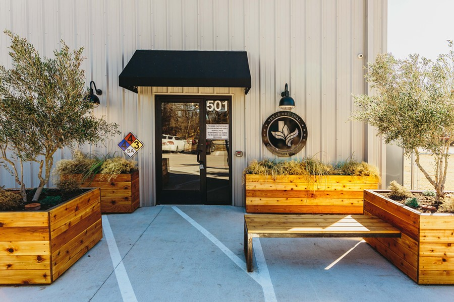 The exterior of Texas Original Cannabis Company (TOCC). An activated retail entry adds ambiance to the nondescript metal agricultural structure.