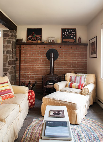 "Former owners added a wood stove to the - downstairs ""great room."" Stewart has surrounded the space with cozy chairs to create a nook for reading or guests. Since buying the house, she's had many friends - move to the area, and befriended many locals. - PHOTO: DEBORAH DEGRAFFENREID"