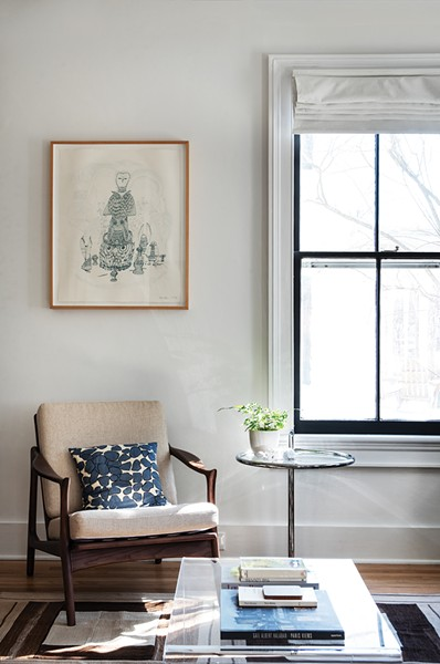 "A corner nook of Walker's downstairs living room was created by closing up an extra kitchen door. The sketch above the chair is a limited-edition print Walker bought in Brooklyn. One particular task she loves is - helping clients hang art. ""I think it's something I'm very skilled at. People often don't know how to hang work or the right space to hang it. Sometimes beautiful pieces - are hidden away somewhere,"" she says. - PHOTO: DEBORAH DEGRAFFENREID"
