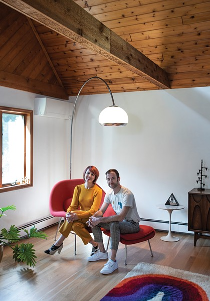 """Hilary Davis and Jordan Moser on their Eero Saarinan """"Womb Chair"""" under the Arc Lamp, made by the Guzzini brothers in Italy. Moser found the iconic Midcentury Modern lamp on Craigslist in the dead of winter. """"It had seen better days,"""" Moser remembers. """"The head had been ripped off, the sockets removed—it was in pieces."""" Still, he drove up to Woodstock in his Honda Civic """"with fingers crossed"""" and was able to score the piece for $125. """"For a moment it seemed like it wasn't going to fit in the back,"""" he recalls However, after some dissembling, he was soon driving down the thruway with the lamp hanging out the back window. After an additional $20 investment and a """"night doing surgery,"""" he was able to surprise Davis with a new lamp arcing over the living room. """"That was my favorite part,"""" says Moser. """"She got so excited; we did a little dance in the living room."""" - PHOTO: DEBORAH DEGRAFFENREID"""