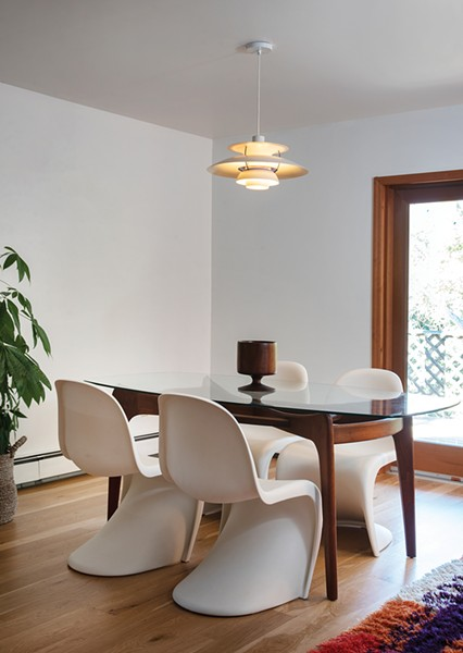 """The dining room features a glass dining table designed by furniture designer-turned-shipbuilder Adrian Pearsall, Verner Panton single-injection plastic chairs, and a Louis Polson PH-5 pendant lamp. """"We love the personalities of the designers from that era and the stories about their projects and artistic endeavors. They were all renaissance people,"""" says Davis. - PHOTO: DEBORAH DEGRAFFENREID"""
