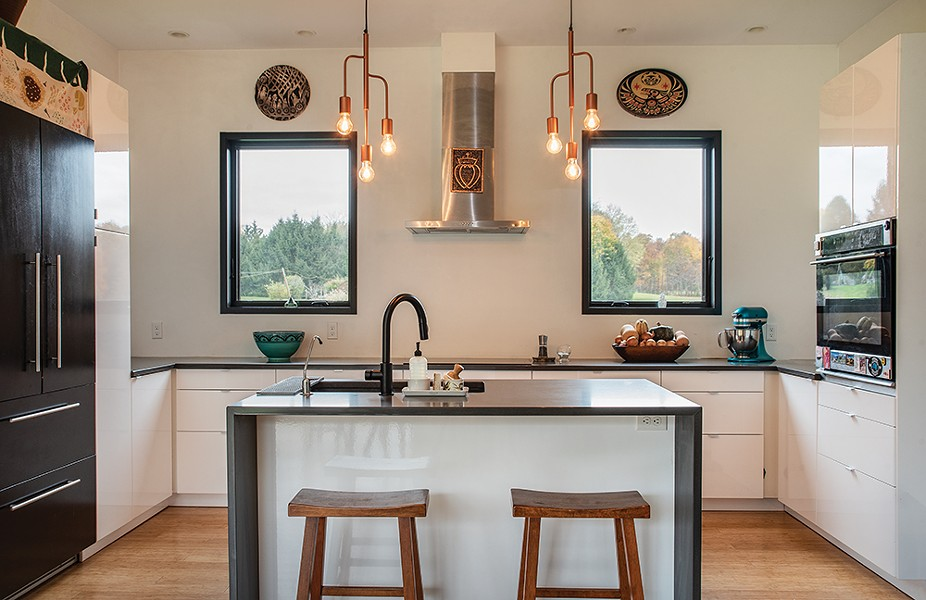 The kitchen, under two west-facing windows. The couple designed the home to have smaller windows along the west side of the house to protect from the warmer afternoon sunlight and keep the home cooler. - PHOTO: DEBORAH DEGRAFFENREID