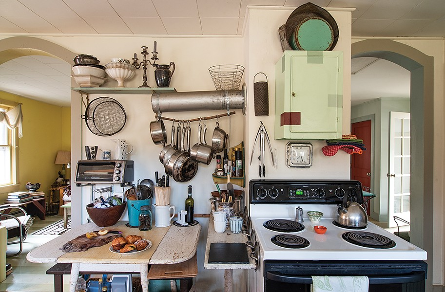 """In the kitchen, Feinberg removed a wood - burning cook stove but kept the stove pipe, reappropriating it as a hanging pot rack. Inspired by paint swatches, she repainted the cabinets with random, geometric splashes of color. The experiment in kitchen redecorating then worked its way into her creative work, with similar geometric squares of varied color showing - up in her oil paintings. """"It really diverged from the type of work I had been doing years before,"""" she explains. - PHOTO: DEBORAH DEGRAFFENREID"""