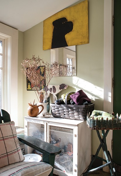 At the entrance of Feinberg's apartment, she created a sunny landing and mudroom area by shifting the bathroom to an adjacent closet. Feinberg bought the bright yellow painting of a dog by outsider artist and local legend Earl - Swanigan on the street in Hudson. - PHOTO: DEBORAH DEGRAFFENREID