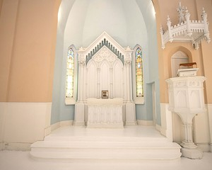 """In redesigning the space Bokaer left the church's original sanctuary and pulpit intact. """"I wanted to keep everything very respectfully as it was,"""" Bokaer says. With original stained glass windows on either side, the gothic style reredos—the carved centerpiece directly behind the altar—features columns topped with busts of St. Matthew. The crowned pulpit occasionally doubles as a DJ booth."""