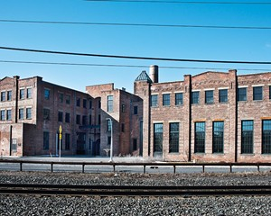 The former US Curtain Factory. Once a thriving manufacturing center, in 2013 the building was converted into 55 units of affordable artist housing; including studios, one-, two-, and three-bedroom units with varying layouts, as well as share-studio and gallery spaces.