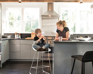 """Dunja Von Stoddard and her son Lars in the kitchen. The space was rebuilt from the ground up (including the south facing back wall, which had sustained fire damage and needed to be completely replaced), but the wooden ceiling beams are original.""""I wanted to bring it back in a modern way that was still appreciative of an old farmhouse,"""" says Von Stoddard."""