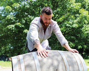 Todd Cavallo rolls a barrel into the yard to use as a tasting table.