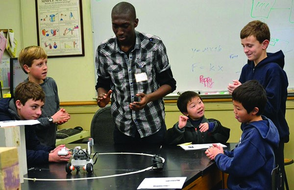 Oakwood Friends School alumnus Kwabena Arthur (class of 2013) working with participants of the Oakwood Friends School Sunday Robots program. Kwabena is currently a student at MIT.
