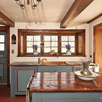 Robert Sweeney and Eddie Cattuzzo's Flatbush Stone Home Wooden countertops and broad beams reflect the warmth of morning sunlight in the kitchen.