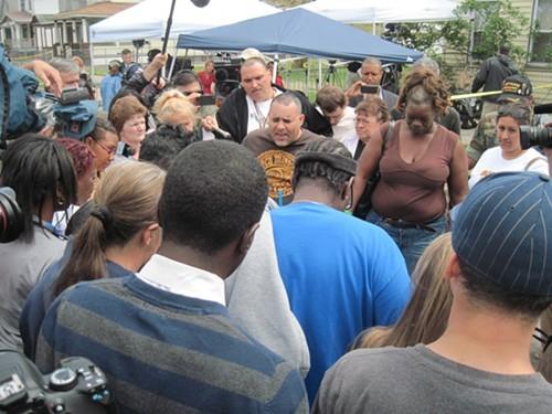 Angel Lozada leads the crowd in a prayer vigil May 8 on Seymour Avenue.