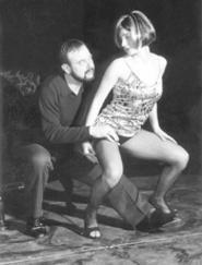Dermatologist Larry (Terry Burgler) inspects the skin - of Alice (Jodi Dominick).